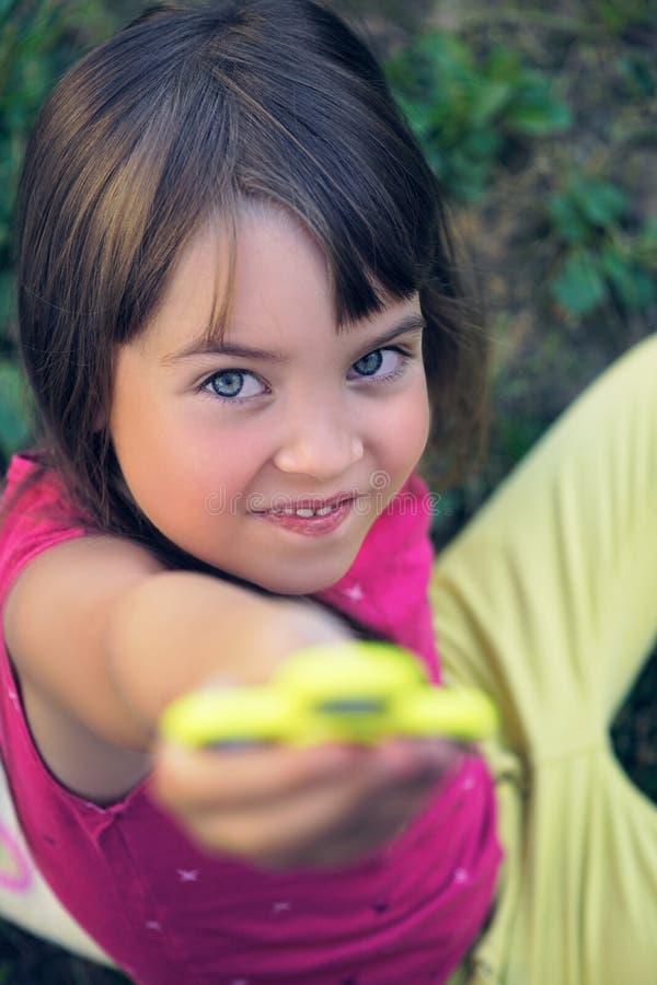 拿着普遍的坐立不安锭床工人玩具-接近的画象的年轻女小学生 库存照片