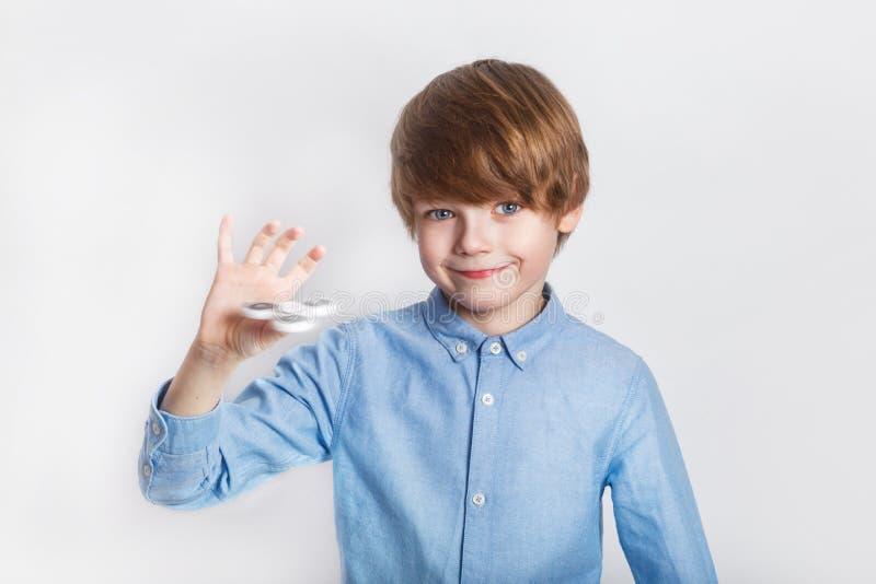 拿着普遍的坐立不安锭床工人玩具-接近的画象的年轻男孩 使用与锭床工人的愉快的微笑的孩子 库存图片