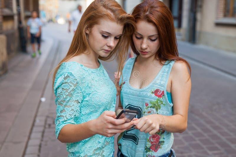 拿着智能手机和信用卡的两个俏丽的女孩 都市backg 免版税图库摄影