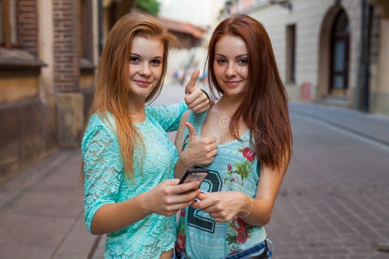 拿着智能手机和信用卡的两个俏丽的女孩 都市backg 免版税库存图片