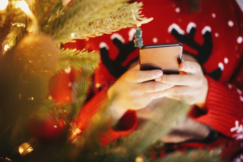 拿着智能手机和浏览互联网金黄c的美丽的女孩 库存照片