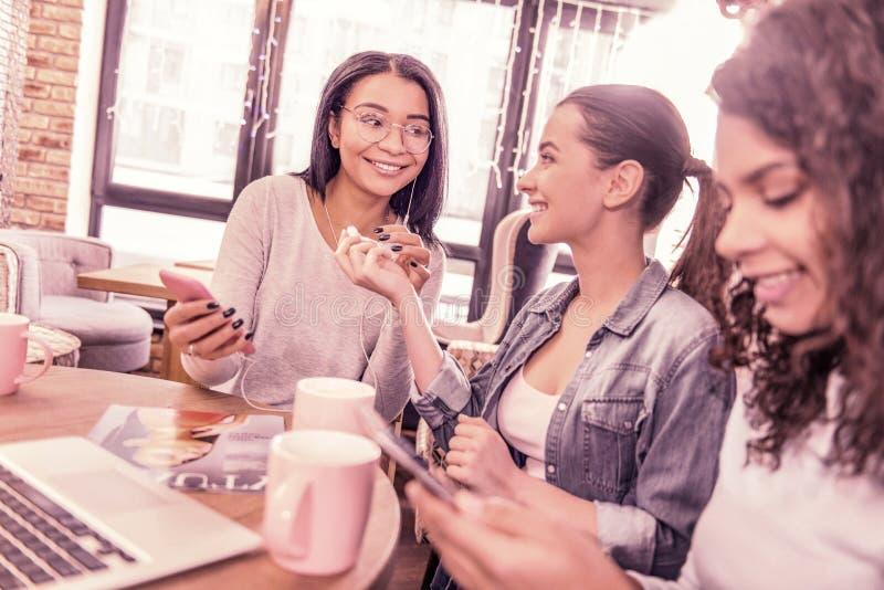 拿着智能手机和耳机的妇女戴着眼镜听到音乐 免版税库存照片