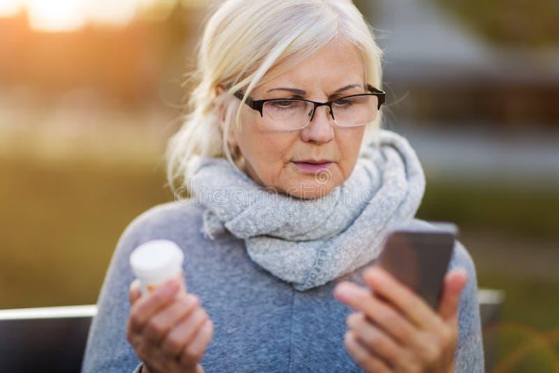 拿着智能手机和药瓶的妇女 免版税库存图片