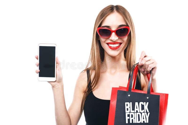 拿着智能手机和购物袋的性感的妇女 库存图片