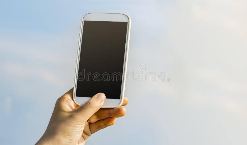 拿着智能手机的人对天空 免版税库存照片