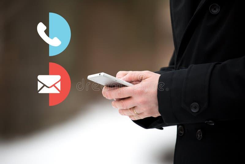 拿着智能手机的商人流动在一个多雪的冬日 外套的人 联络我们电话和电子邮件象,客服 图库摄影
