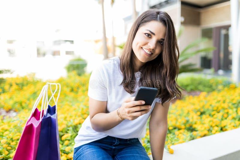 拿着智能手机的妇女,当坐由在购物之外时的袋子 库存照片