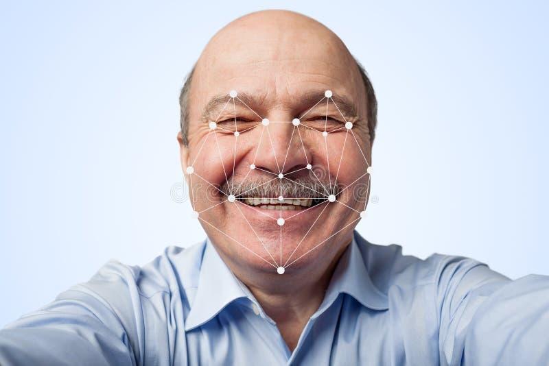 拿着智能手机的年长人穿过面部公认 免版税库存照片