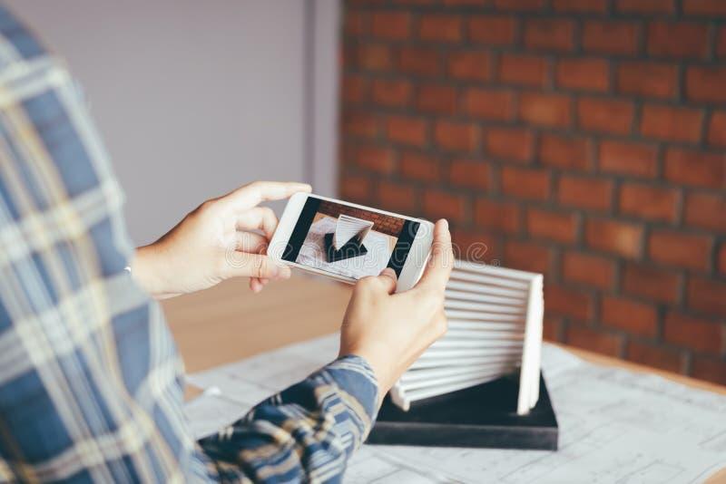 拿着智能手机的建筑师人拍architectu的照片 库存照片