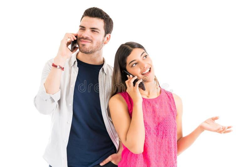 拿着智能手机的愉快的夫妇在演播室 库存照片