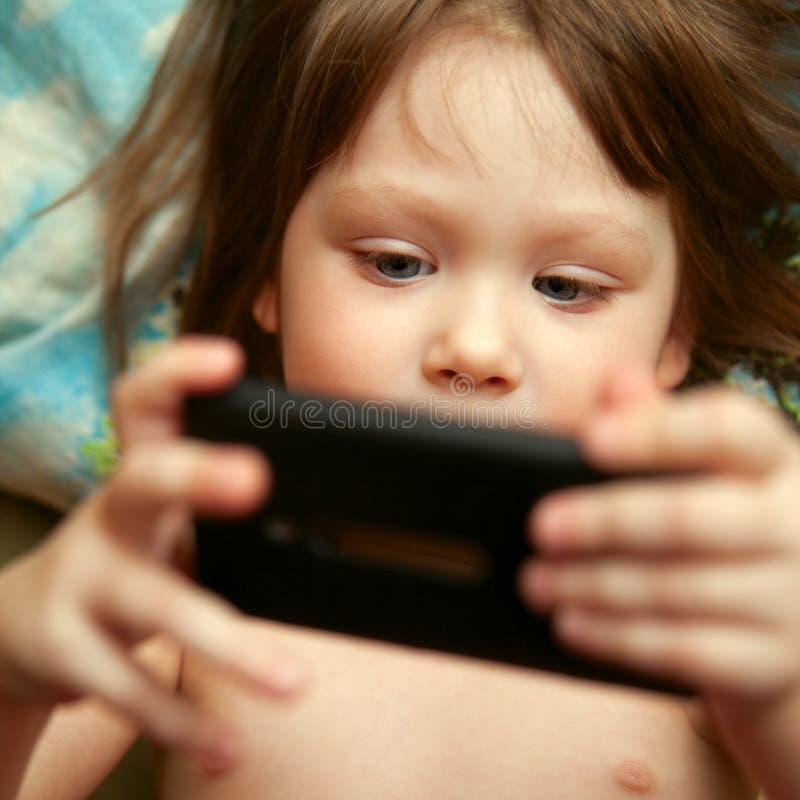 拿着智能手机的愉快的逗人喜爱的小女孩 库存图片