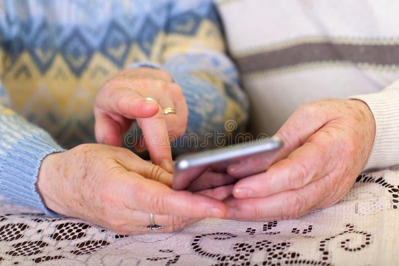 拿着智能手机的年长手 库存照片