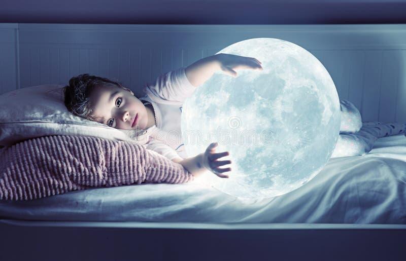 拿着月亮的一逗人喜爱的女孩的艺术画象 库存照片
