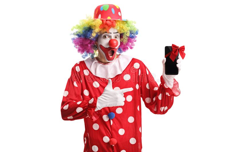拿着有一把红色弓的一个手机和指向它的愉快的微笑的小丑 免版税图库摄影