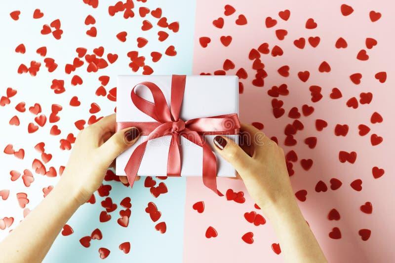 拿着有丝带的女性手礼物盒在蓝色和桃红色背景,顶视图 免版税库存照片