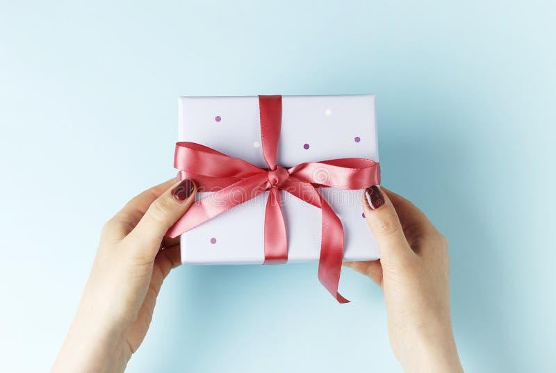 拿着有丝带的女性手礼物盒在蓝色背景,顶视图 库存图片