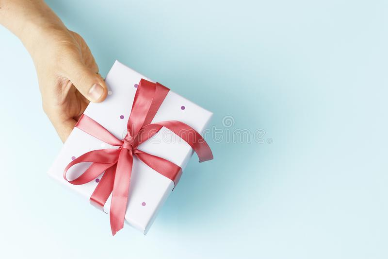 拿着有丝带的男性手礼物盒在蓝色背景,顶视图,拷贝空间 免版税库存图片