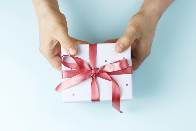 拿着有丝带的男性手礼物盒在蓝色背景,顶视图 库存图片