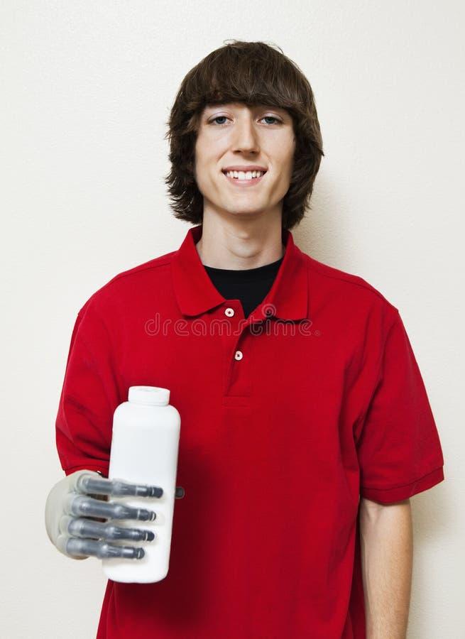 拿着有义肢的一个愉快的年轻人的画象瓶移交灰色背景 库存图片