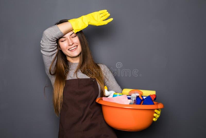 拿着有事的一个桶清洗的和微笑在灰色背景的防护手套的年轻疲乏的妇女 免版税库存图片