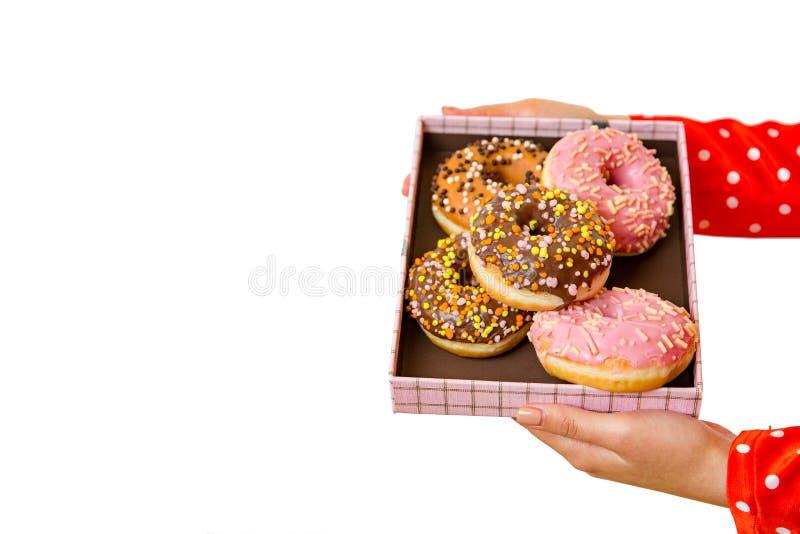 拿着有五颜六色的油炸圈饼的女性手箱子在白色背景 孤立 库存图片