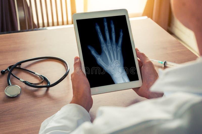 拿着有右手的X-射线的医生一种数字片剂 听诊器和注射器在书桌上 骨关节炎概念 免版税库存图片