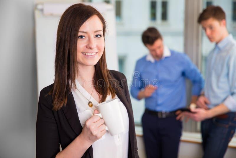 拿着有同事的微笑的女实业家咖啡杯谈论 库存图片