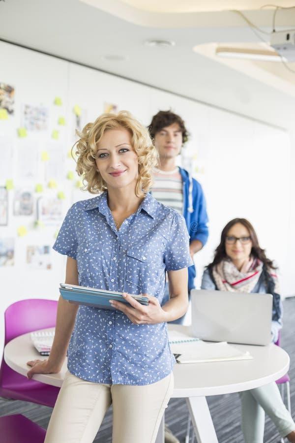 拿着有同事的美丽的女实业家画象数字式片剂在背景中在创造性的办公室 库存图片