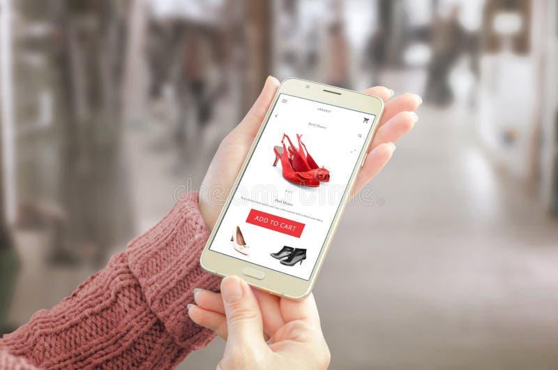 拿着有商务网站的妇女巧妙的电话 与妇女鞋子的用户友好的app接口 免版税库存图片