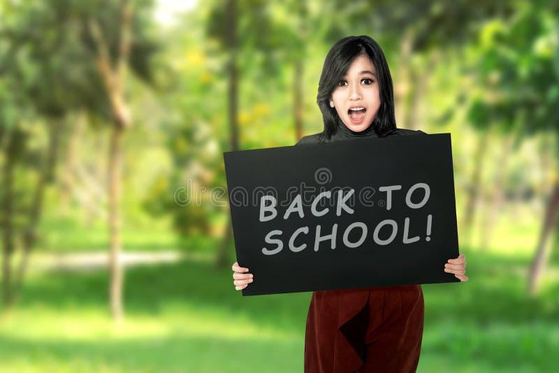 拿着有回到学校的年轻亚裔学生女孩委员会 免版税库存图片