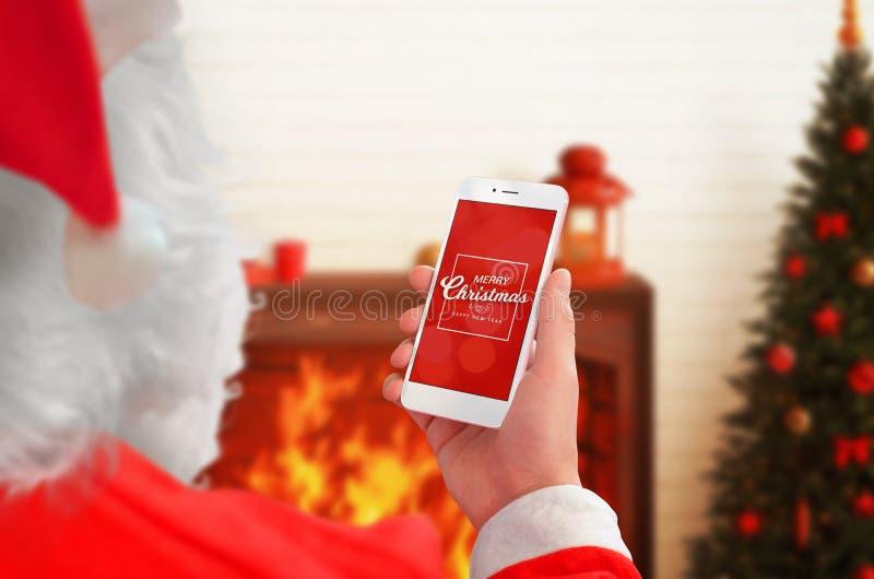 拿着有圣诞节问候的圣诞老人手机在显示 免版税图库摄影