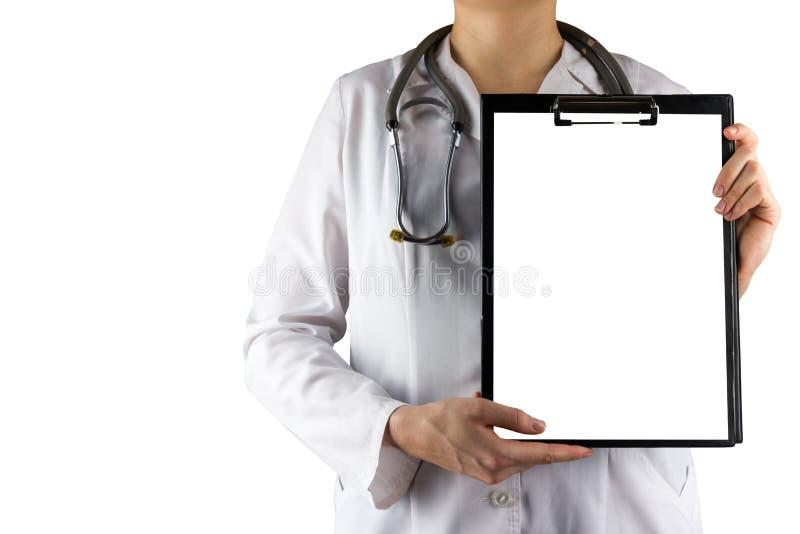 拿着有在白色背景和听诊器隔绝空白的纸片的女性医生的手医疗剪贴板 免版税库存图片