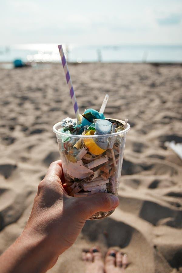 拿着有垃圾的在海滩垃圾,塑料,瓶,泡沫,垃圾的手塑料杯子 污染地球的生态概念 库存照片