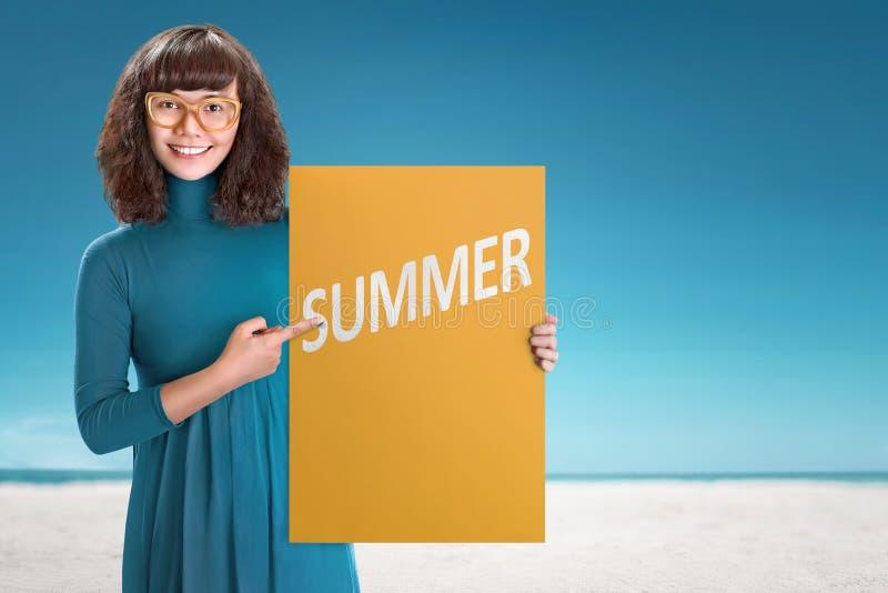 拿着有夏天标志的年轻亚裔妇女委员会 免版税库存照片