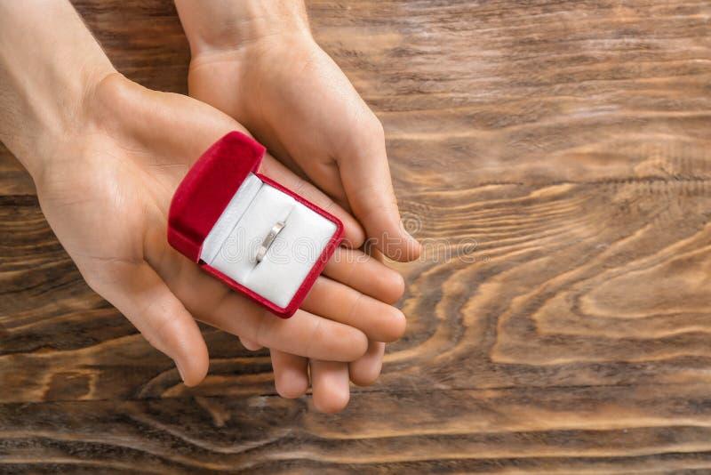 拿着有定婚戒指的男性手箱子在木背景 库存照片