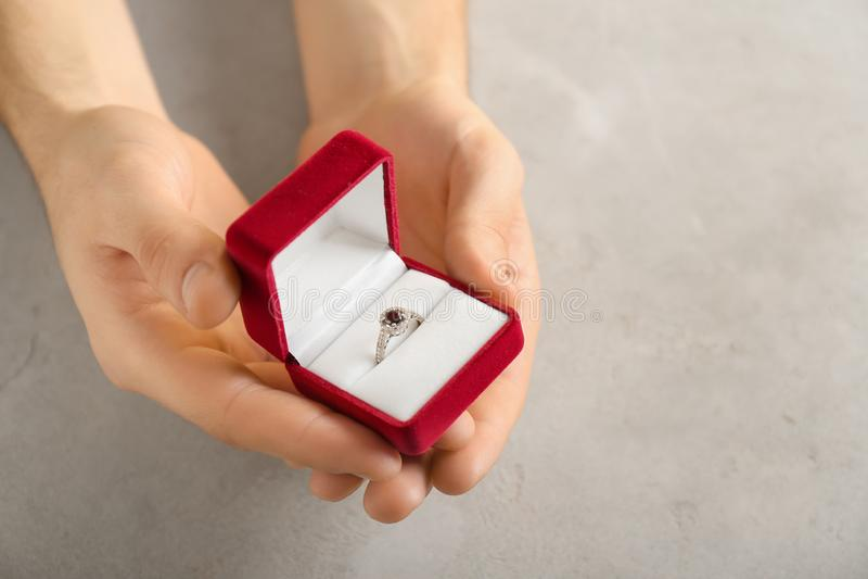 拿着有定婚戒指的男性手箱子在灰色背景 图库摄影