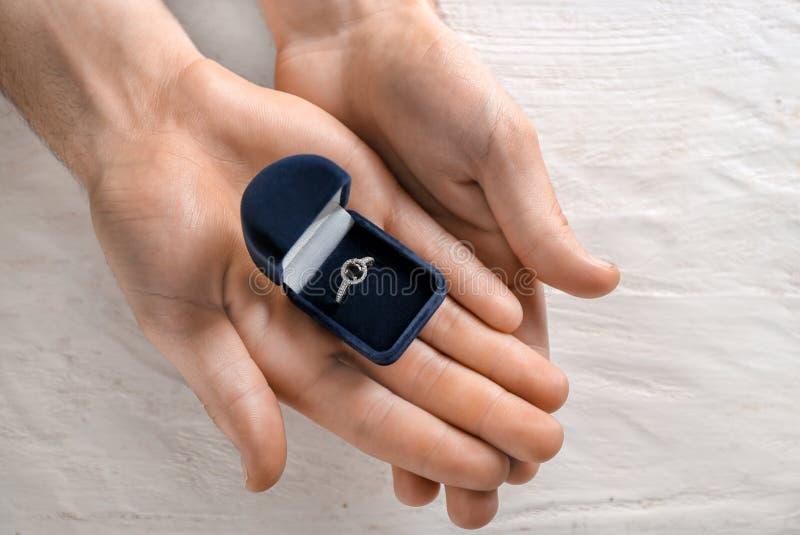 拿着有定婚戒指的男性手箱子在轻的木背景 免版税库存照片
