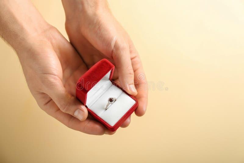 拿着有定婚戒指的男性手箱子在颜色背景 库存照片