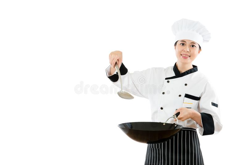 拿着有小铲烹调的微笑的厨师铁锅 免版税库存图片