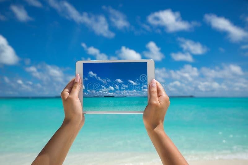 拿着有屏幕的妇女片剂计算机在热带海 T 库存照片