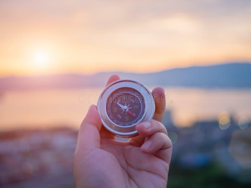拿着有山和日落天空的特写镜头手指南针 库存图片