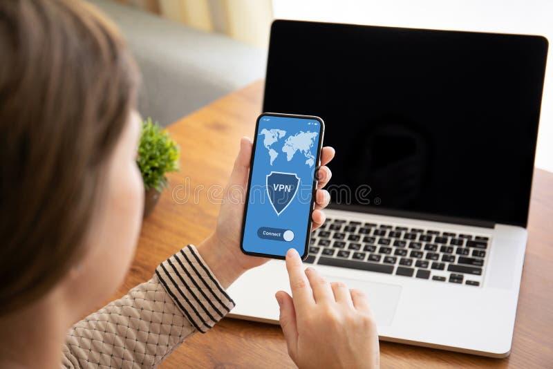 拿着有应用程序vpn的女性手接触电话在屏幕上 免版税库存图片