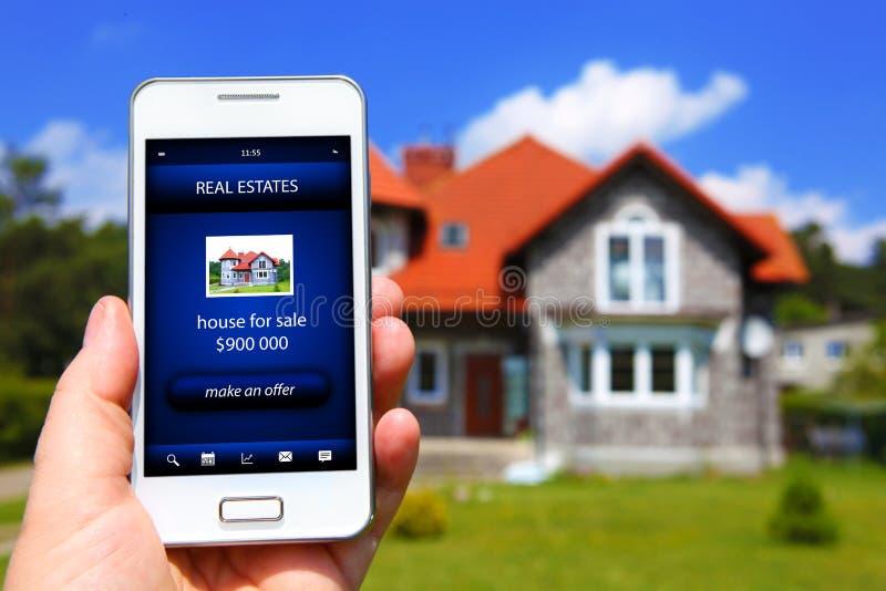 拿着有房子销售提议的手手机 免版税库存照片