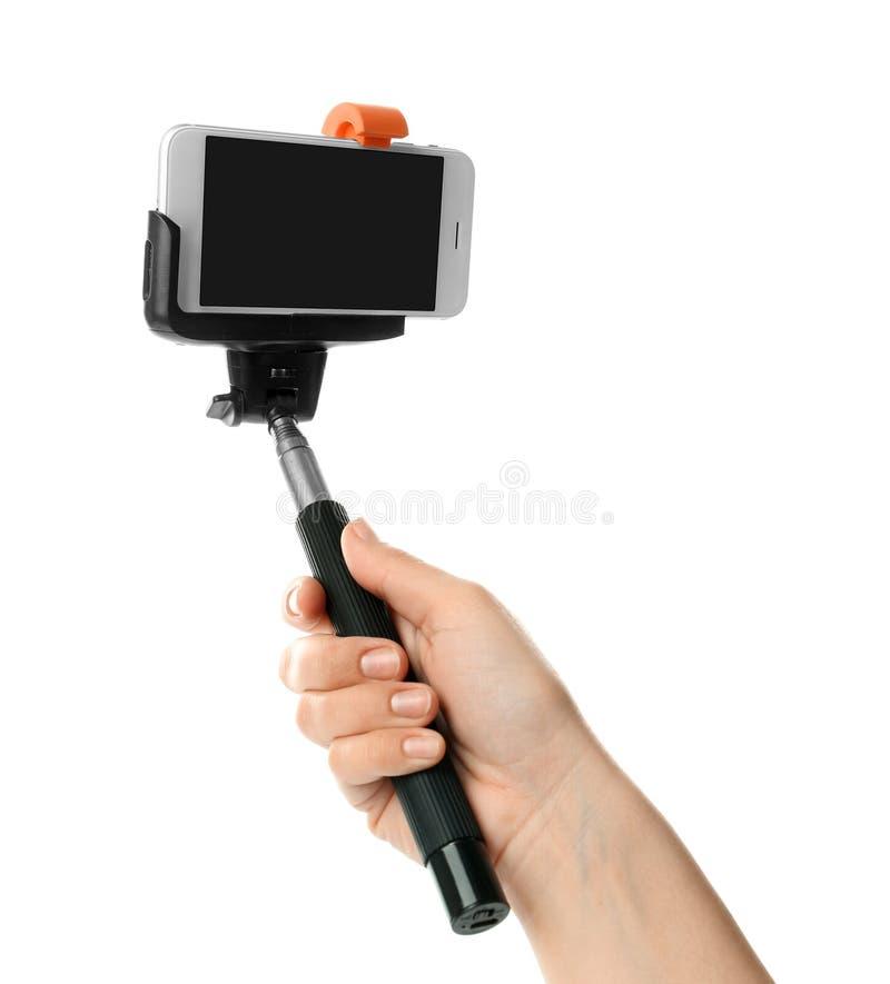 拿着有手机的妇女selfie棍子 免版税库存图片