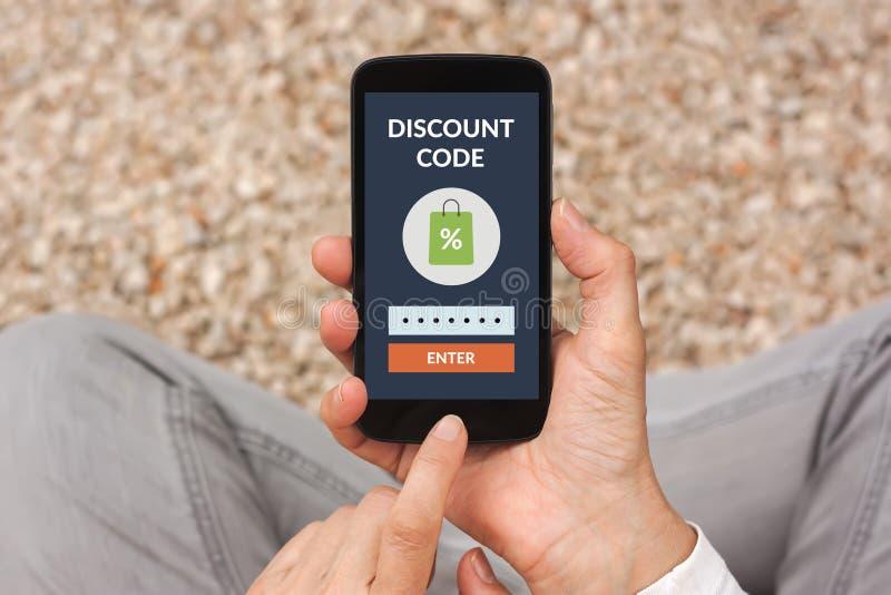 拿着有折扣代码概念的手巧妙的电话在屏幕上 免版税库存图片