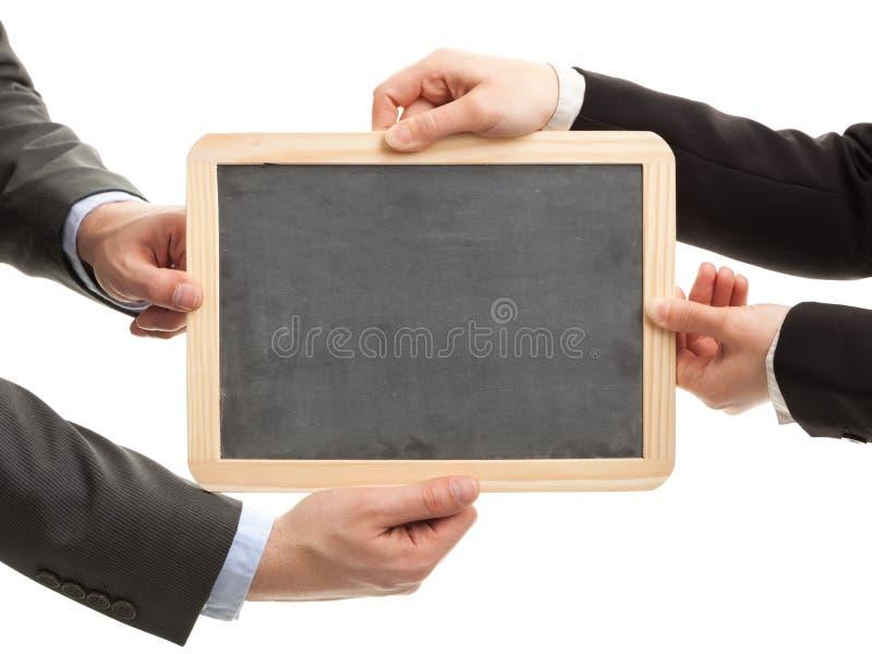 拿着有拷贝空间的商人和妇女空的黑板 事务、教育和通信概念 库存照片