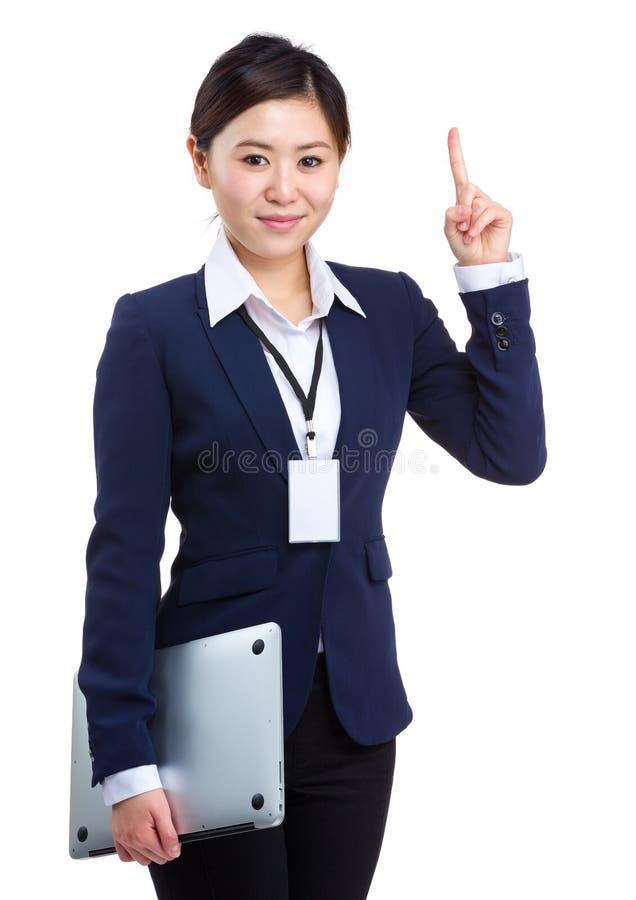 拿着有指点的女实业家膝上型计算机 库存图片