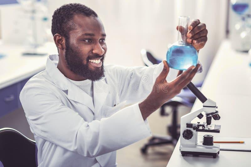 拿着有新的疫苗的聪明的化工工作者玻璃管 库存图片