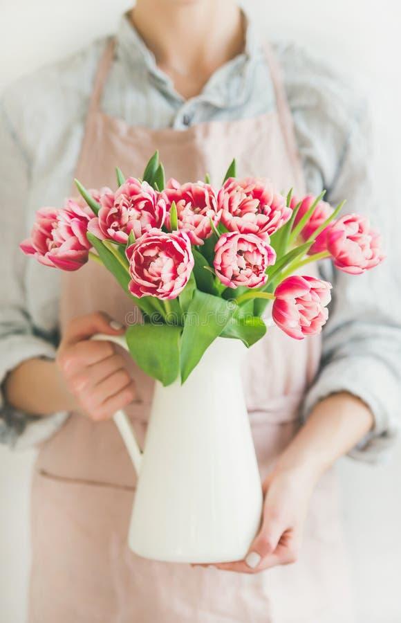 拿着有新鲜的桃红色郁金香的妇女白色搪瓷花瓶 免版税库存图片