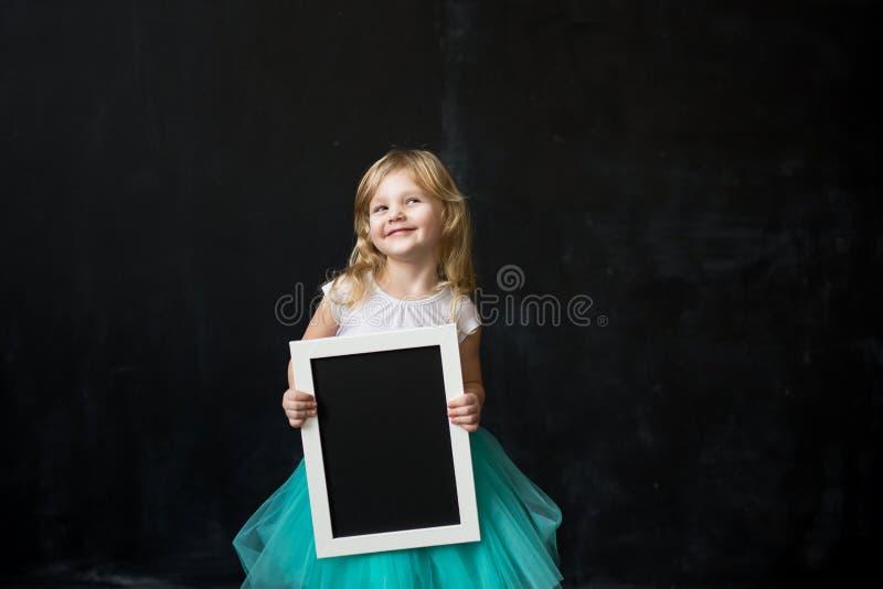 拿着有木制框架的女孩空的黑板 库存图片